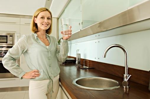 Femme qui boit un verre d'eau sans calcaire grâce à son adoucisseur d'eau