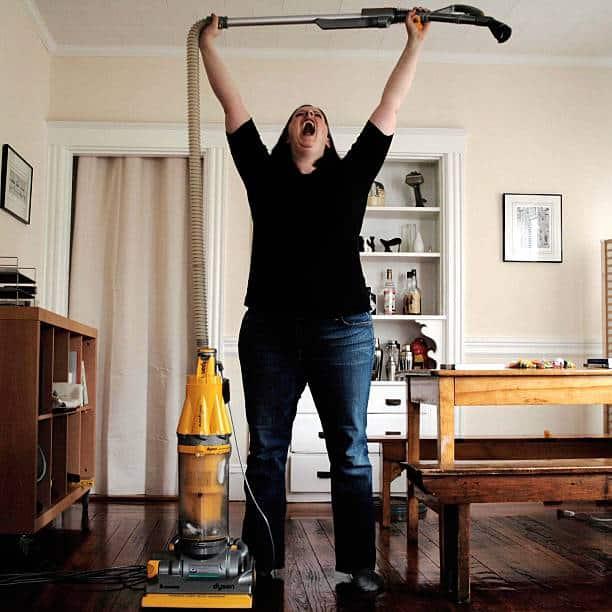 Femme qui tend en l'air le flexible de son aspirateur Dyson en signe de victoire