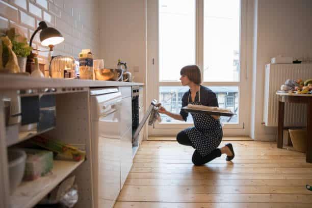 Femme qui met un plat au four dans sa cuisine